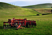 tractor blades on green pasture