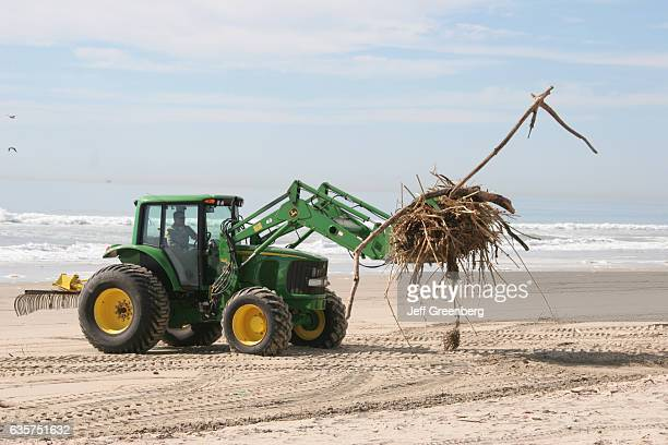 A tractor cleaning up debris on Huntington State Beach