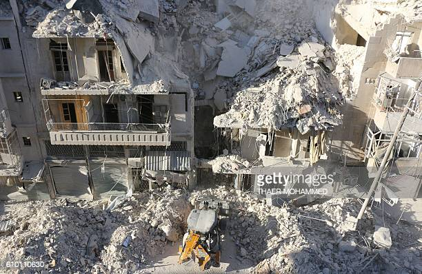 A tractor clears the rubble following Syrian govermnet forces airstrikes in the rebel held neighborhood of Tariq aBab in Aleppo on September 24 2016...