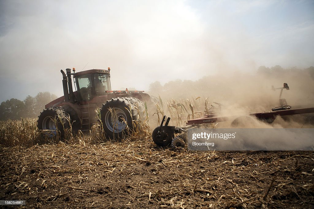 'BEST PHOTOS OF 2012' (): A tractor cuts down corn in a field designated as zero yield on a farm in Vigo County near Terre Haute, Indiana, U.S., on Tuesday, July 31, 2012. The U.S. Department of Agriculture has declared more than half the counties in the country natural disaster areas as drought sears millions of acres of pasture and cropland. Photographer: Victor J. Blue/Bloomberg via Getty Images