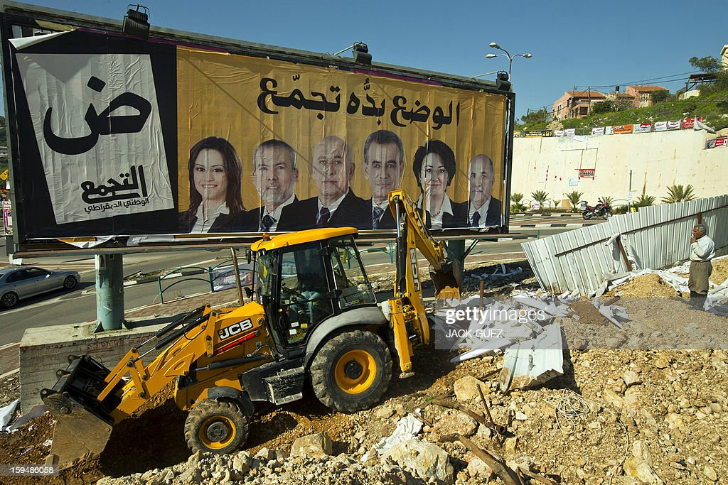 A tractor demolishes a fence in front of an election campaign poster of Israeli-Arab candidates running for the parliamentary elections in the Arab-Israeli town of Umm al-Fahm on January 14, 2013. Arab-Israelis, descendants of the 160,000 Palestinians who stayed on after the creation of Israel in 1948, make up 20 percent of the population. PHOTO / JACK GUEZ