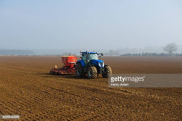 Tractor drilling seed in ploughed field on misty morning