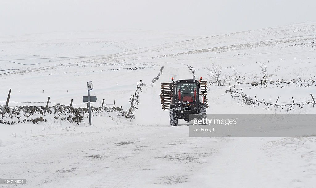 A tractor drives along a snow covered road near to Kirkby Stephen in Cumbria on March 27, 2013 in Kirkby Stephen, England. Heavy snow continues to fall in some parts of the country as Britain suffers the coldest March in 50 years.