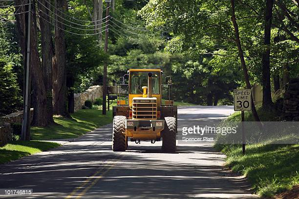 A tractor drives up a rural street while working on a country club that is being expanded on the edge of a forested area on June 7 2010 in Easton...