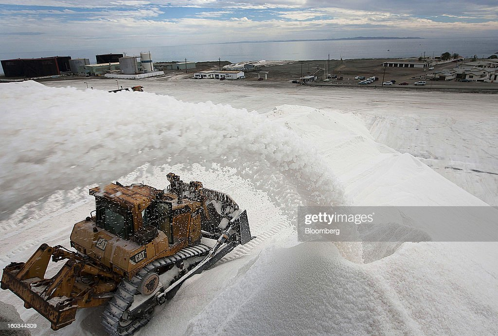 A tractor moves salt being poured into a pile at the Exportadora de Sal (ESSA) salt-transshipment facility on Cedros Island off the coast of Guerrero Negro, Mexico, on Wednesday, Jan. 24. 2013. Exportadora de Sal (ESSA), a joint venture between Fidecomiso Mining Development Corporation and Mitsubishi, is one of the leading producers and suppliers of salt for the chlorine-alkali industry in the Pacific Rim. Photographer: Susana Gonzalez/Bloomberg via Getty Images