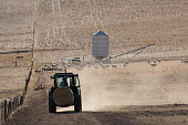 A backlit photograph of a tractor carrying a bale of hay and kicking up some dust on a dry but picturesque farm in Central Western NSW, Australia. A backlit photograph of a tractor carrying a bale of