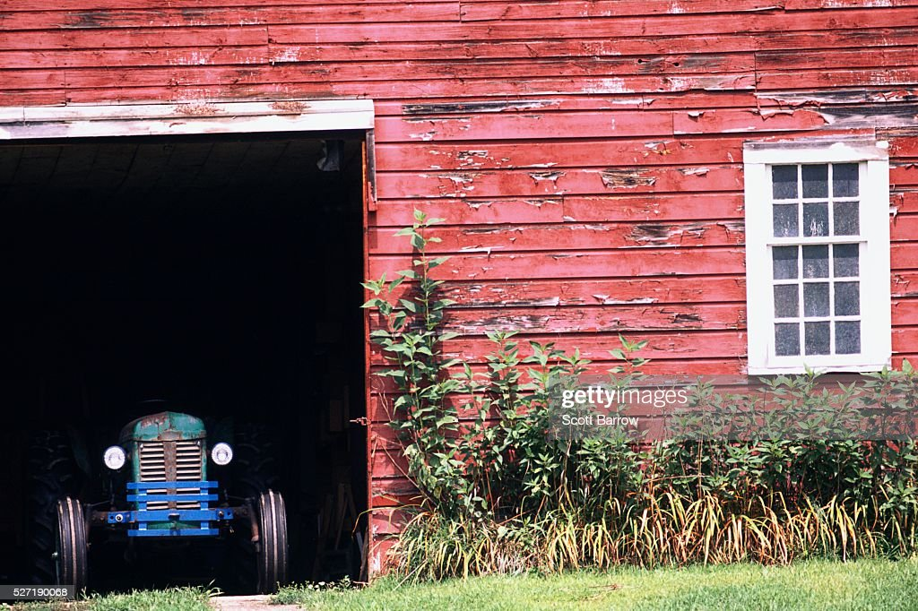 Tractor parked in a barn : Foto de stock