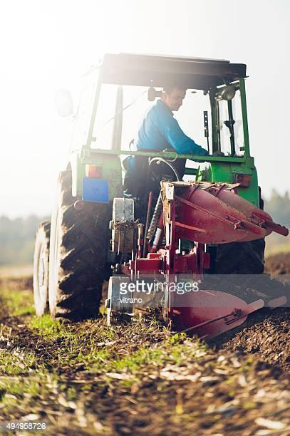Tracteur ploughing sur le terrain dans la lumière du soleil