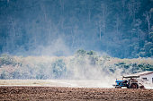 Tractor Plowing Field Against Trees