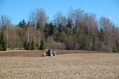 Tractor plows the earth near the forest. Arable spring land.