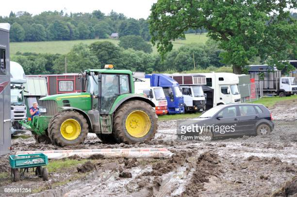 Tractor pulling car out of the muddy car park at the Yorkshire Show 2012 which was cancelled due to bad weather