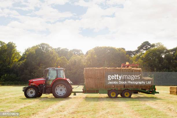 Tractor pulling trailer and hay bales in farm field