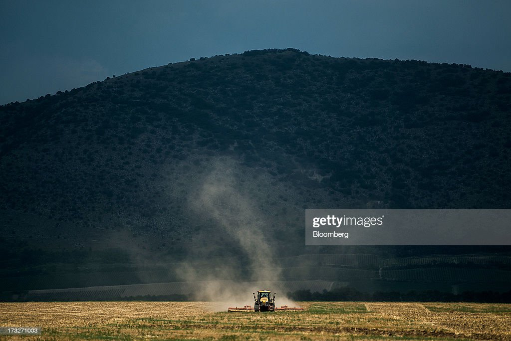 A tractor pulls a plough across a grain field in Csipotelek, Hungary, on Wednesday, July 10, 2013. The world's grain harvest will be bigger in the 2013-14 season than predicted a month ago on increased estimates for corn in China and larger wheat crops in India and Canada, the International Grains Council said. Photographer: Akos Stiller/Bloomberg via Getty Images