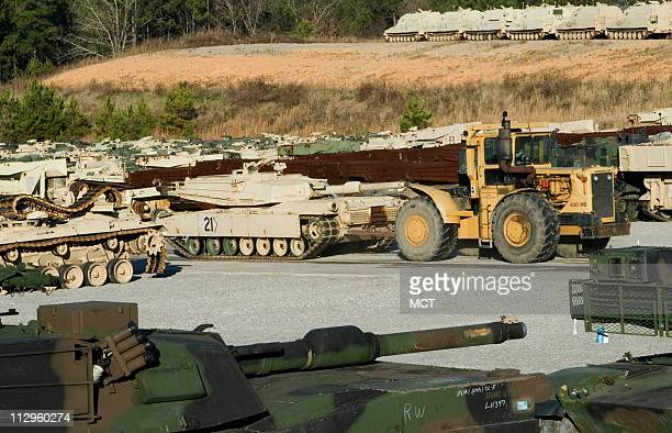 A tractor pulls an M1A1 tank from a storage yard on Tuesday December 5 at the Anniston Army Depot in Anniston Alabama where military heavy equipment...