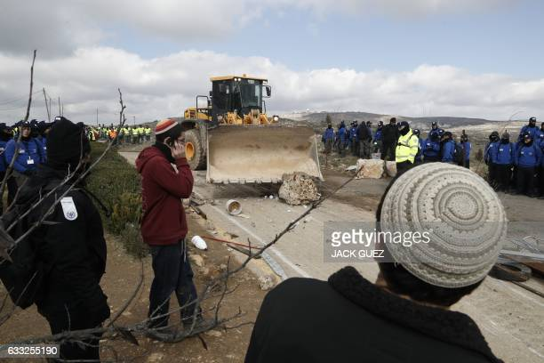 TOPSHOT A tractor removes debris blocking a road at the Amona outpost northeast of Ramallah on February 1 2017 as Israeli security forces evict the...