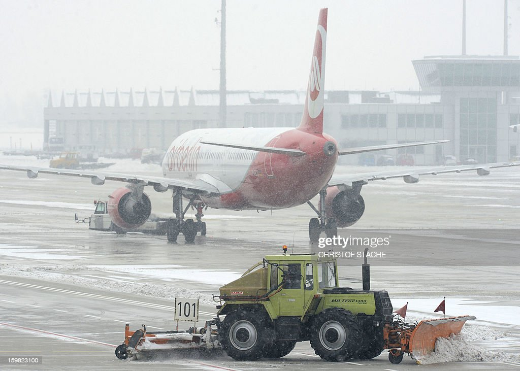 A tractor removes snow from the ground around an Air Berlin airplane at the Franz-Josef-Strauss airport in Munich, southern Germany, during snowfall on January 21, 2013. In Munich, Germany's number two airport, some 161 flights -- or more than 15 percent -- were already cancelled due to the weather today. STACHE