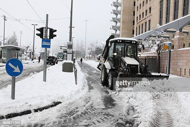 A tractor shovels snow on a road beside a light rail track Jerusalem Israel February 20 2015