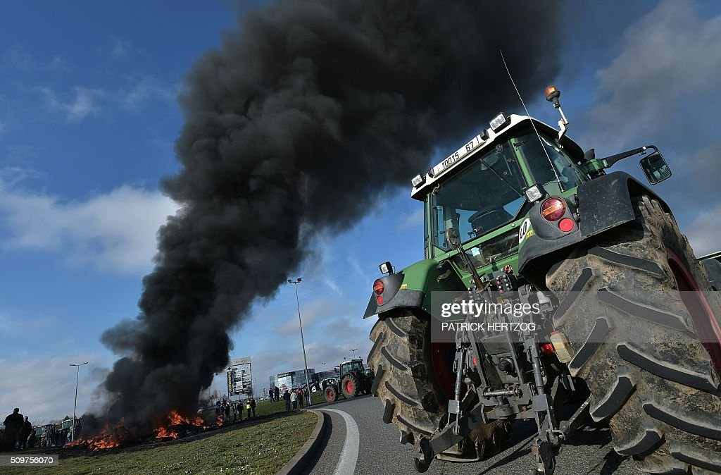 A tractor stands next to burning tyres in Vendenheim, eastern France on February 12, 2016, during a protest of farmers against increasing constraints and charges, the collapsing prices of cereals, milk and vegetables, caused in part by the sanctions on Russia, as well as rising fertiliser prices. / AFP / PATRICK HERTZOG