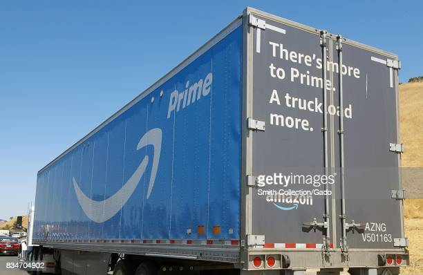 Tractor trailer semi truck with logos for Amazon Prime service and text reading 'There's more to Prime a truckload more' traveling on the 680 Freeway...