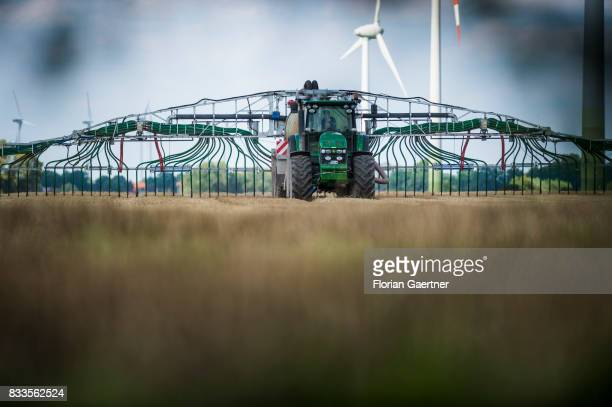 A tractor with a liquidmanure tanker and a rearmounted injector fertilizes a field on August 14 2017 in Goldbeck Germany
