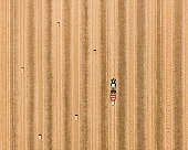 Tractor with bales of hay in field, aerial view