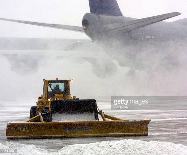 A tractor works to remove snow near a United Airlines terminal at Chicago''s O''Hare International Airport as a departing United Airlines 747...