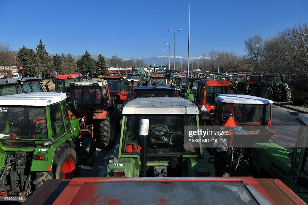 Tractors line the highway in front of the customs post at the border crossing of Promachonas between Greece and Bulgaria, in northern Greece, as farmers set up a blockade of customs offices, shutting down the movement of trucks to and from Bulgaria on February 7, 2016. Greek farmers protesting against pension reforms heightened highway and border protests around the country, piling pressure on the leftist government of Prime Minister Alexis Tsipras. The mobilisation which began in mid-January has created tractor blockades at dozens of highway locations and key border crossings to Bulgaria and Turkey, which the farmers intermittently open for a few hours each day. / AFP / SAKIS MITROLIDIS