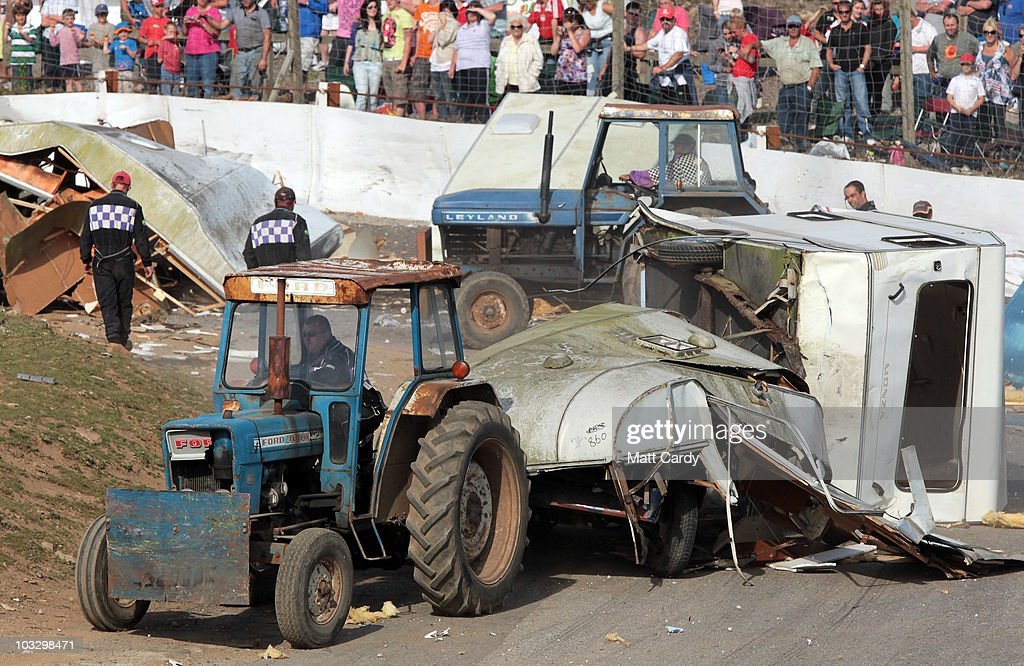 Tractors move the wreckage of old caravans that have been destroyed in the annual Cornish Caravan Chaos at United Downs Raceway on August 8 2010 near...