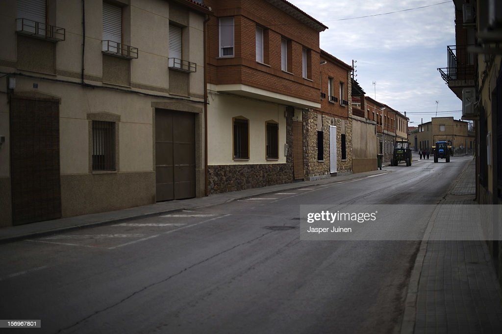 Tractors pass through emplty streets on November 23, 2012 in Villacanas, Spain. During the boom years, where in its peak Spain built some 800,000 houses a year accompanied by the manufacturing of millions of wooden doors where needed, the people of Villacanas were part of Spain's middle class enjoying high wages and permanent jobs. During the construction boom years the majority of the doors used within these new developments were made in this small industrial town. Approximately seven million doors a year were once assembled here and the factory employed a workforce of almost 5700 people, but the town is now left almost desolate with the Villacanas industrial park now empty and redundant. With Spain in the grip of recession and the housing bubble burst, Villacanas is typical of many former buoyant industrial Spanish towns now struggling with huge unemployment problems.