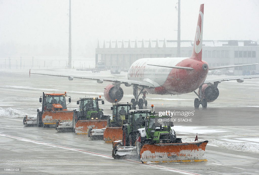 Tractors remove snow from the ground around an Air Berlin airplane at the Franz-Josef-Strauss airport in Munich, southern Germany, during snowfall on January 21, 2013. In Munich, Germany's number two airport, some 161 flights -- or more than 15 percent -- were already cancelled due to the weather today. STACHE
