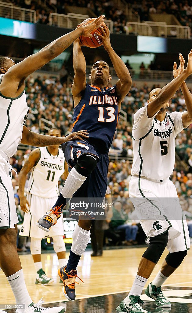 Tracy Abrams #13 of the Illinois Fighting Illini drives to the basket between Adreian Payne #5 and Derrick Nix #25 of the Michigan State Spartans at the Jack T. Breslin Student Events Center on January 31, 2013 in East Lansing, Michigan. Michigan State won the game 80-75.