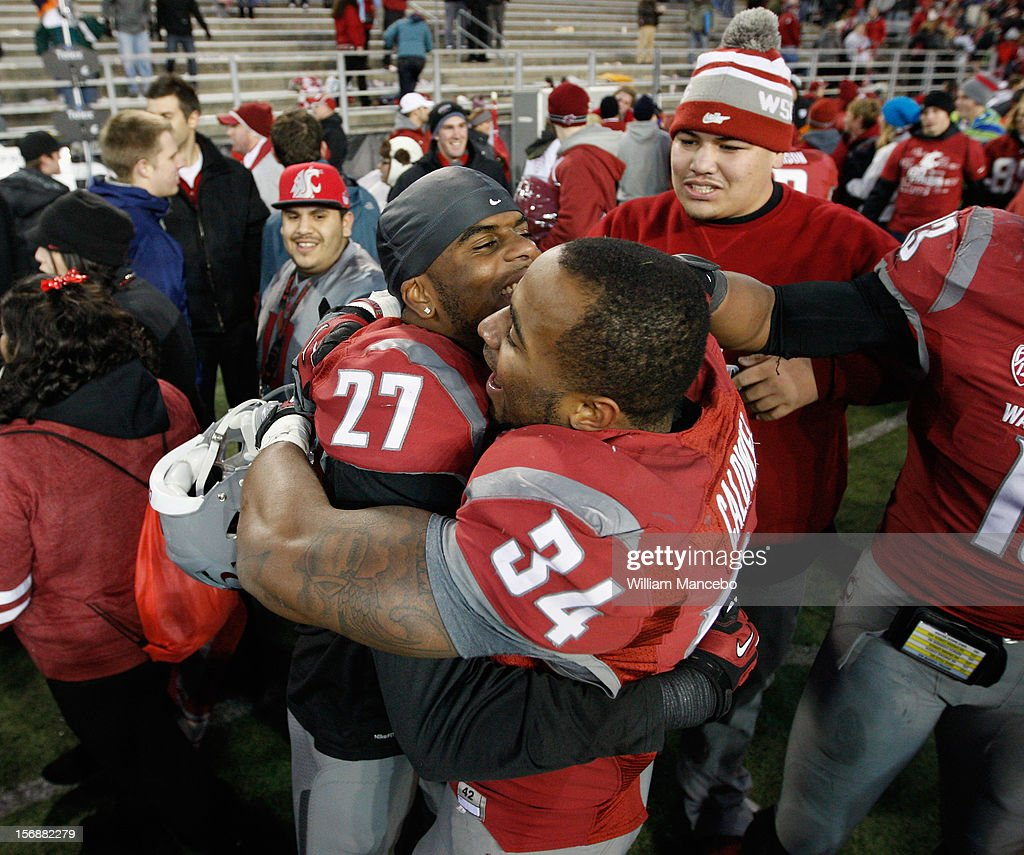 Tracy Clark #27 and Teondray Caldwell #34 celebrate as the Cougars win the Apple Cup 31-28 during overtime against the Washington Huskies at Martin Stadium on November 23, 2012 in Pullman, Washington.