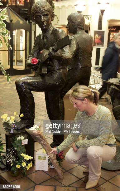 Tracy Kershaw from Liverpool lays flowers at a statue in the Cavern Walks shopping Mall in the city of former Beatles bassist George Harrison who it...
