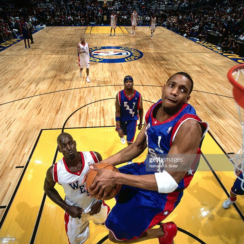 Tracy McGrady of the Eastern Conference AllStars dunks against Kevin Garnett of the Western Conference AllStars during the 2004 AllStar Game on...