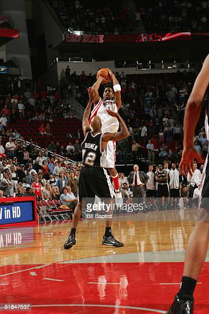 Tracy McGrady of the Houston Rockets attempts and makes a 3pt shot over Bruce Bowen of the San Antonio Spurs with 112 December 9 2004 at the Toyota...