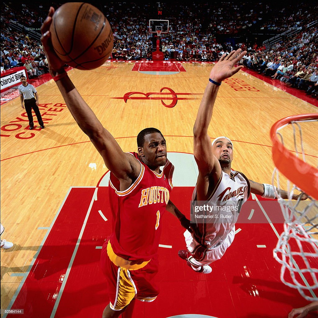 Tracy McGrady #13 of the Houston Rockets drives to the basket for the slam dunk past Drew Gooden #90 of the Cleveland Cavaliers during an NBA game on March 24, 2005 at the Toyota Center in Houston, Texas.