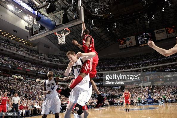 Tracy McGrady of the Houston Rockets dunks on Shawn Bradley of the Dallas Mavericks during Game one of the Western Conference Quarterfinals during...