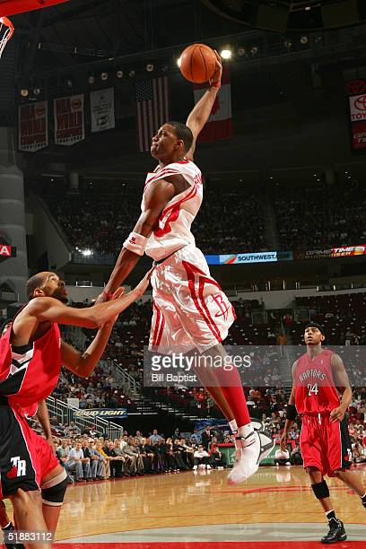Tracy McGrady of the Houston Rockets dunks over Loren Woods of the Toronto Raptors on December 20 2004 at the Toyota Center in Houston Texas NOTE TO...