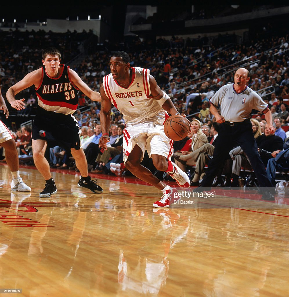 Tracy McGrady of the Houston Rockets moves the ball against Viktor Khryapa of the Portland Trail Blazers during the game at Toyota Center on March 16...