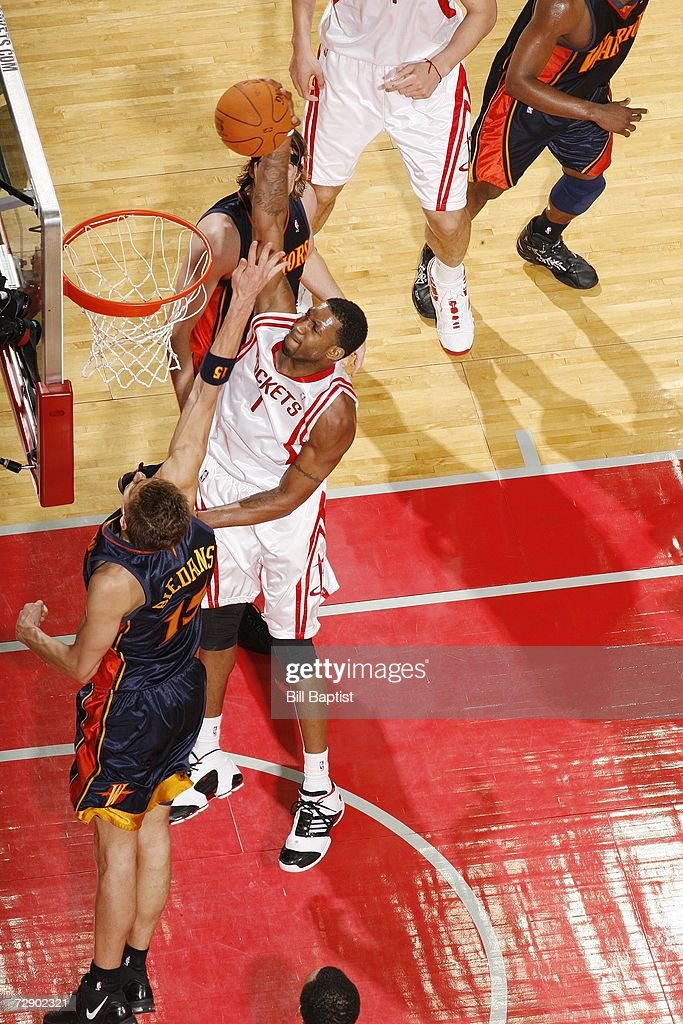 Tracy McGrady of the Houston Rockets powers the ball to the hoop past Andris Biedrins of the Golden State Warriors at the Toyota Center on December 5...