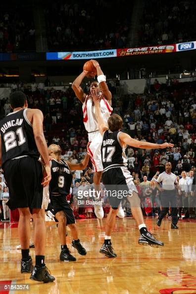 Tracy McGrady of the Houston Rockets shoots the gamewinning 3point shot between Tony Parker and Brent Barry of the San Antonio Spurs on December 9...