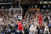 Tracy McGrady of the Houston Rockets shoots the winning shot against Keith Van Horn of the Dallas Mavericks in Game two of the Western Conference...