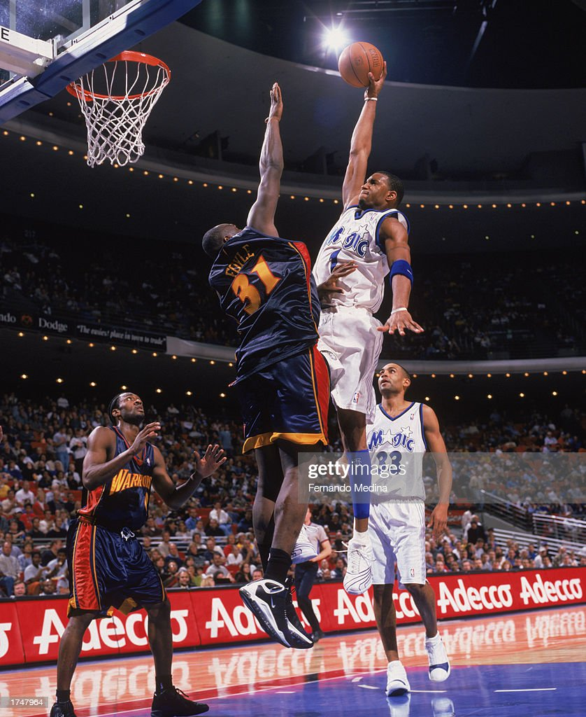 Tracy McGrady #1 of the Orlando Magic dunks over Adonal Foyle #31 of the Golden State Warriors during the game at TD Waterhouse Centre on December 13, 2002 in Orlando, Florida. The Magic won 111-85.