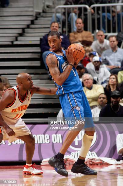 Tracy McGrady of the Orlando Magic holds the ball in the post against Jacque Vaughn of the Atlanta Hawks during the game on December 13 2003 at...