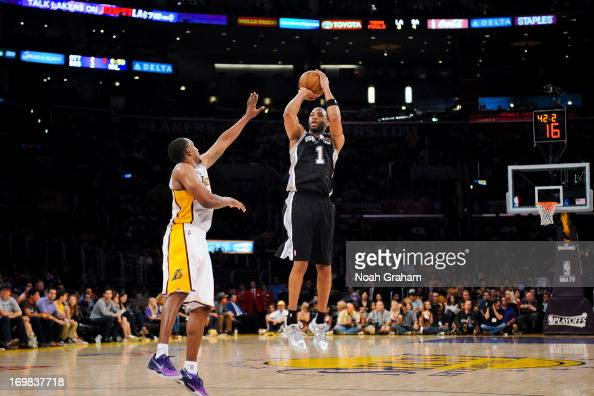 Tracy McGrady of the San Antonio Spurs shoots a threepointer against Chris Duhon of the Los Angeles Lakers in Game Four of the Western Conference...