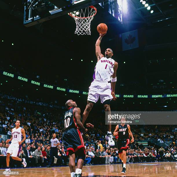 Tracy McGrady of the Toronto Raptors dunks against the Miami Heat circa 2000 at the Air Canada Centre in Toronto Ontario NOTE TO USER User expressly...