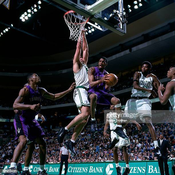 Tracy McGrady of the Toronto Raptors looks to make a play in midair under the basket against the Boston Celtics during an NBA game in Boston...