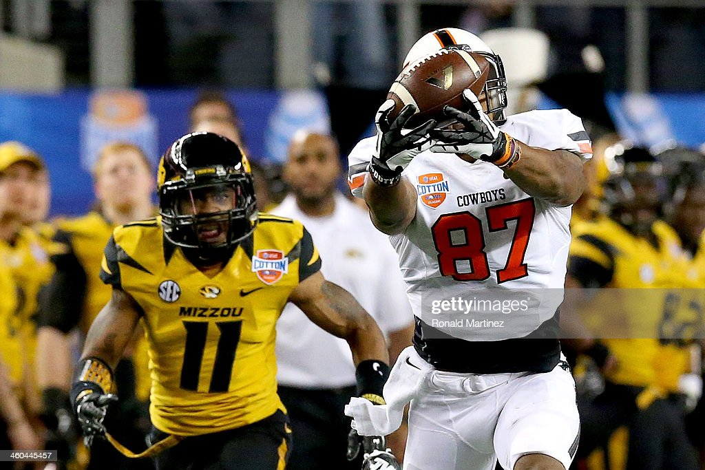 Tracy Moore #87 of the Oklahoma State Cowboys makes a 41-yard catch against Aarion Penton #11 of the Missouri Tigers in the fourth quarter during the AT&T Cotton Bowl on January 3, 2014 in Arlington, Texas.