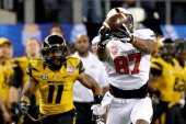 Tracy Moore of the Oklahoma State Cowboys makes a 41yard catch against Aarion Penton of the Missouri Tigers in the fourth quarter during the ATT...