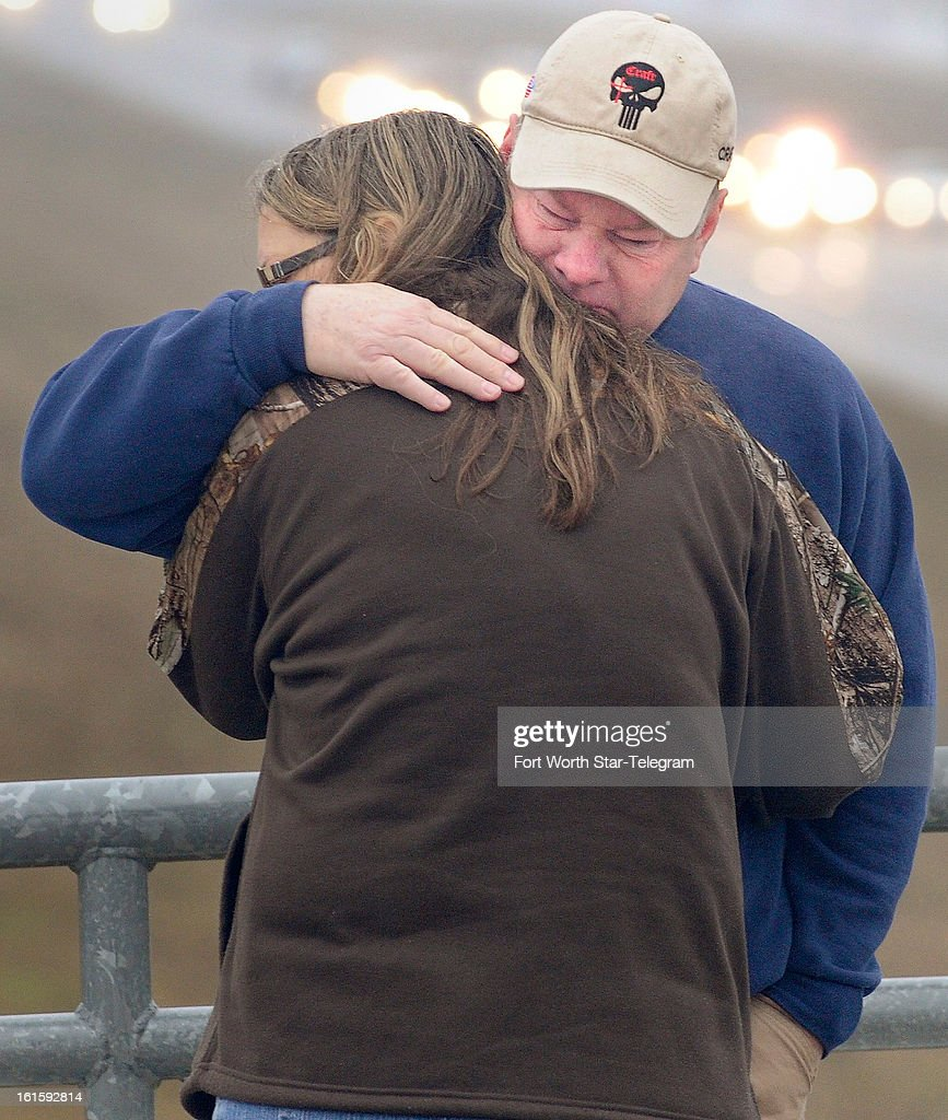 Tracy, right, and Lucinda Larimore, of Henderson, Nevada, embrace after the Chris Kyle procession passes on US 287 in Midlothian, Texas, Tuesday, February 12, 2013.